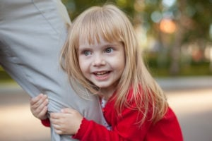 Little girl holding onto parents leg