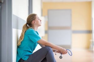 Tired and worried nurse sitting up against the wall holding stethoscope.