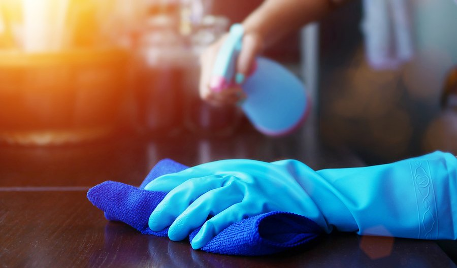 Spraying cleaning solution while wearing blue glove and using a cloth