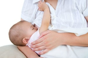 Mom breastfeeding baby in white shirt