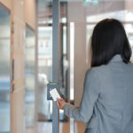 Young business woman holding keycard to get into