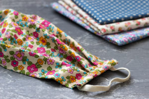Decorative homemade surgical mask and different patterned cloths behind