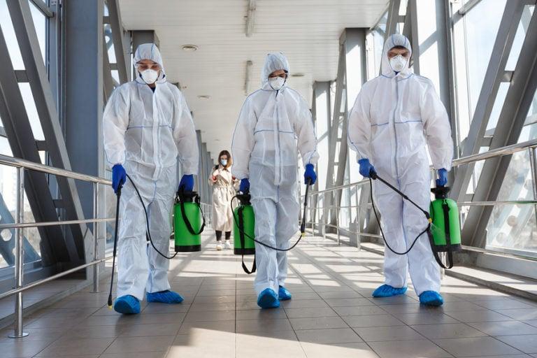 Sanitation crew in hazmat suits spraying down hallway