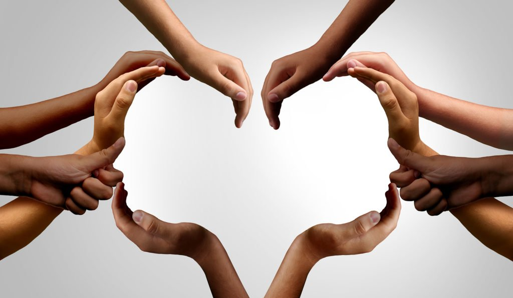 Many hands together forming heart