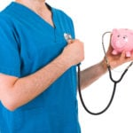Nurse holding stethoscope from piggy bank to chest