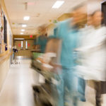 Blurred motion of doctor and nurse pulling stretcher in hospital hallway.
